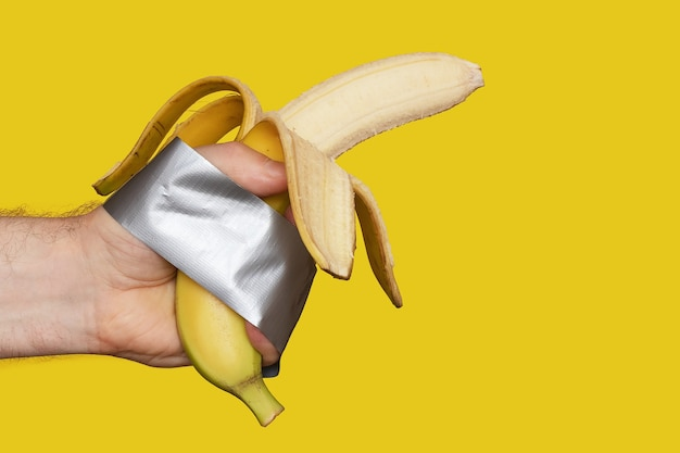 Ripe peeled banana in hand wrapped duct tape isolated on yellow background, fitness nutrition concept, copyspace, close-up