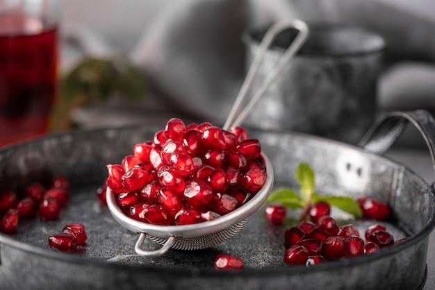 Ripe peeled pomegranate seeds on an iron tray