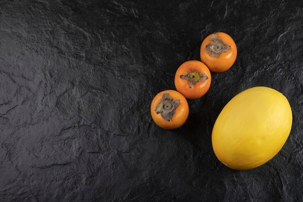 Спелые плоды хурмы и вкусная дыня на черной поверхности