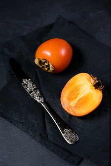 Ripe persimmon, knife on black with copyspace