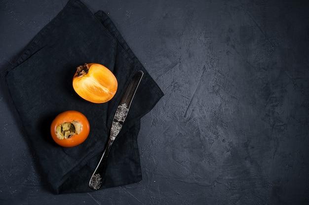 Ripe persimmon, knife on black
