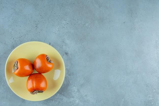 Спелая хурма на тарелке, на мраморном фоне. фото высокого качества