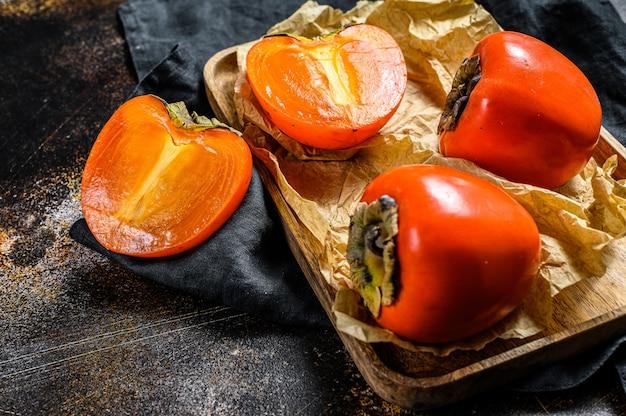 Ripe persimmon on a wooden tray in parchment paper. top view