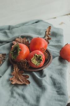 Зрелая хурма на плите глины с листьями на серой предпосылке.