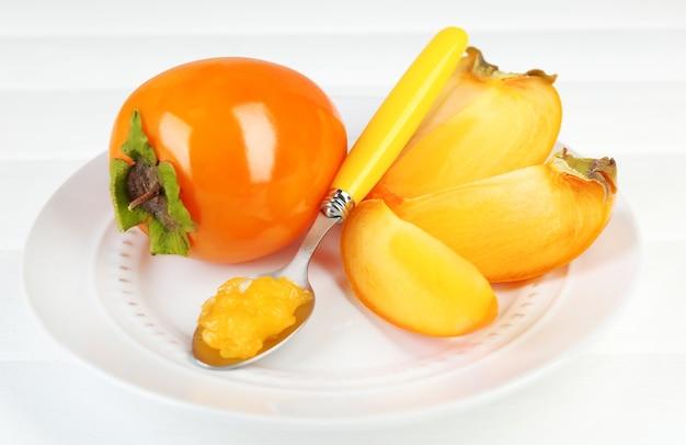 皿、木製のテーブルに熟した柿