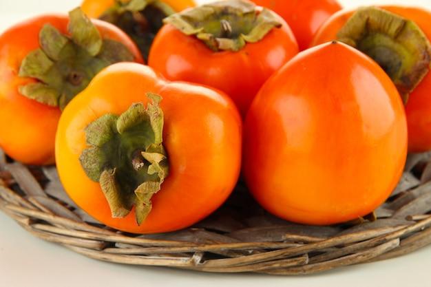 枝編み細工品スタンドの熟した柿のクローズアップ