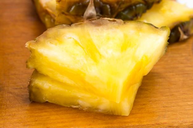 Спелые ананасы и ломтики ананаса на деревянных фоне тропических фруктов.