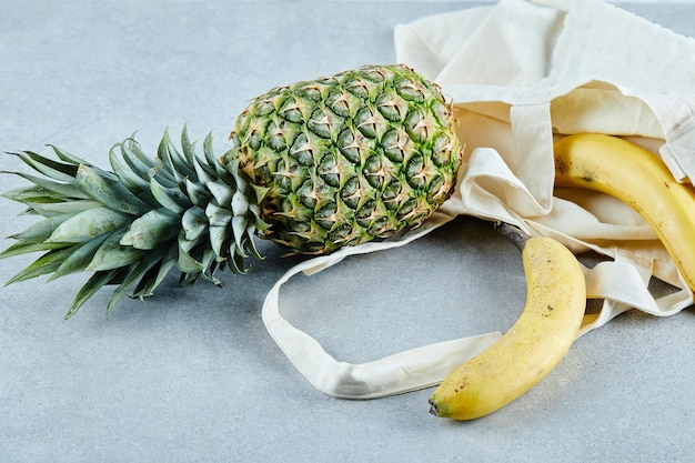 Ananas e banana maturi in un sacchetto bianco sul tavolo blu.