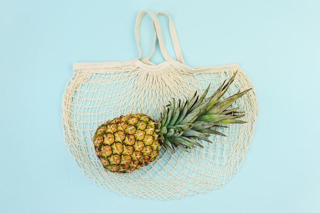 Ripe pineapple over cotton mesh bag