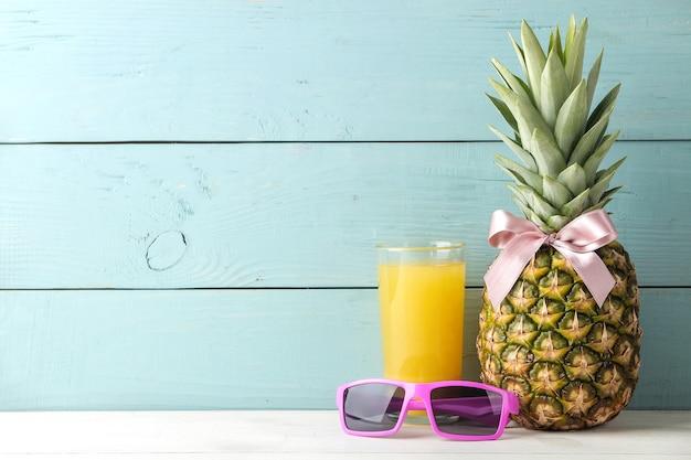 青い木製のテーブルにピンクの弓、サングラス、パイナップルジュースと熟したパイナップルフルーツ。テキストの場所。