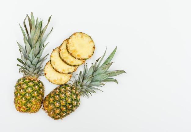 熟したパイナップルのハラとフラットスライスを白に置く