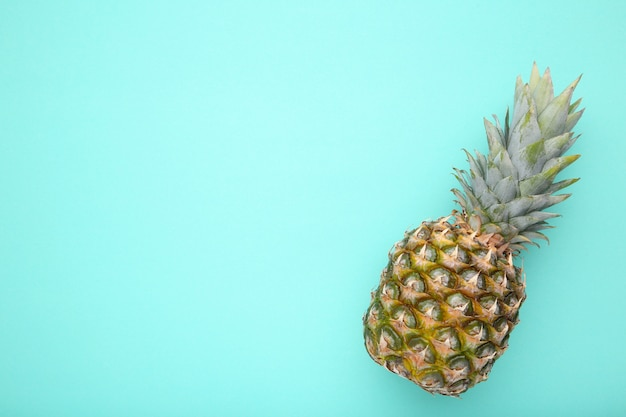 Ripe pineapple on a mint background with copy space