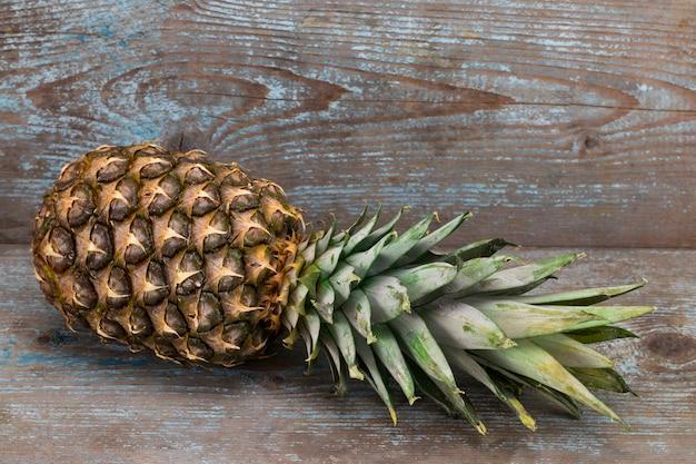 木製の背景の上面に熟したパイナップル
