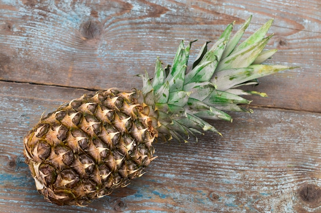 木製の背景の上面図に熟したパイナップル。