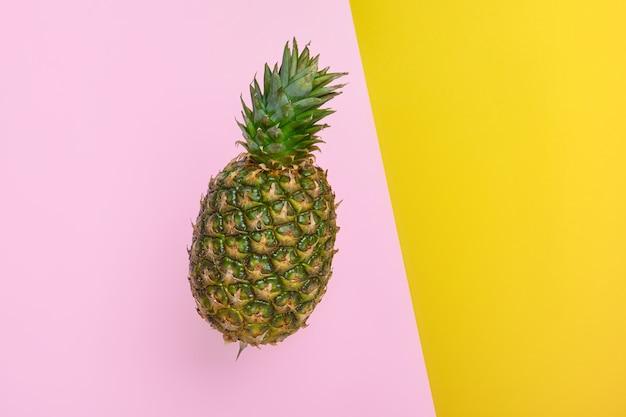 明るい黄色とピンクの背景のコピースペースに熟したパイナップル