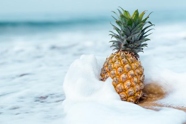 Спелый ананас на золотом песке у океана