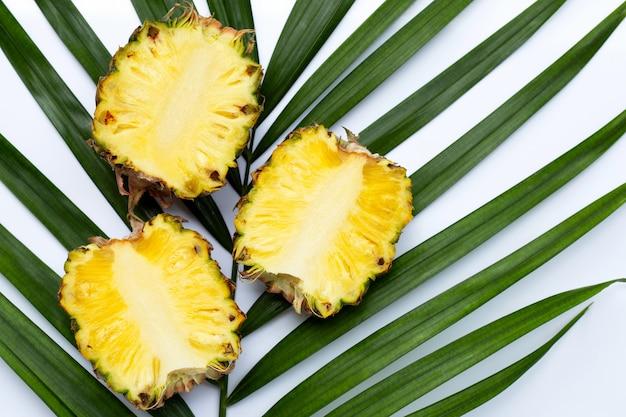 Спелый ананас на тропических пальмовых листьев.