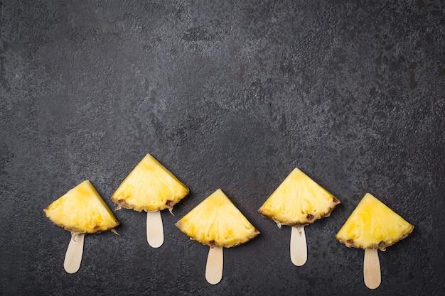 Ripe pineapple slices on sticks on a black background