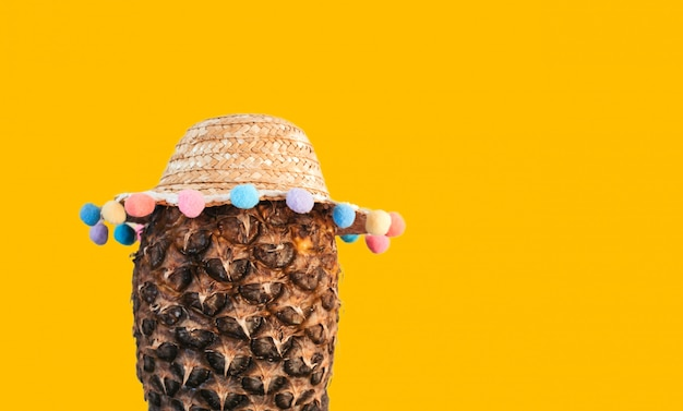 Ripe pineapple in a straw hat with multi-colored pompons on a yellow isolated background copy space.