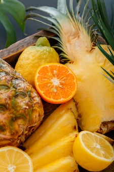 Ripe pineapple. tropical fruits mix wooden box. tangerines oranges pineapples lemons. sliced tropical citrus vitamin dessert as summer background. high quality stock photo