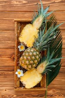 熟したパイナップル。熱帯の夏のフルーツパイナップルの半分と全体のパイナップルは、熱帯のプルメリアの花と木製の箱の茶色の暗いテーブルに。上面図。高品質のストックフォト