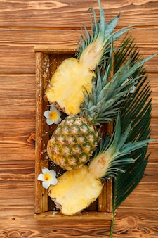 Ripe pineapple. tropical summer fruit pineapple halves and whole pineapple on brown dark table in wooden box with tropical plumeria flowers. top view. high quality stock photo