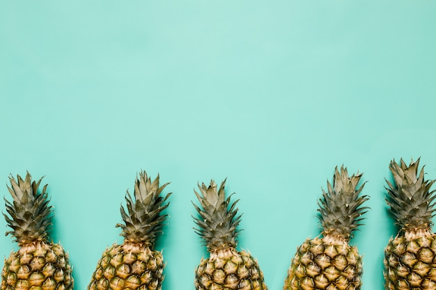 Ripe pineapples border frame on turquoise background isolated. minimalist style trendy tropical concept. empty space for text, copy, lettering.