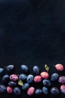 Ripe plum fruits on dark table