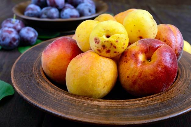 Спелые сливы и абрикосы в керамических мисках на темном деревянном столе