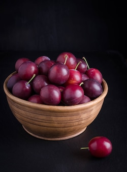 Ripe plums in the bowl on black background