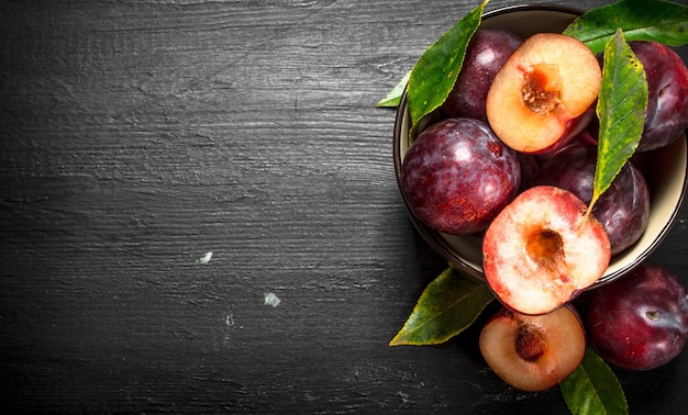 Ripe plums in a bowl. on the black chalkboard.