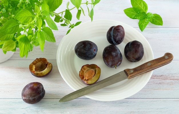 Ripe plums and knife on a white plate and kitchen herbs on a blue painted wood surface.