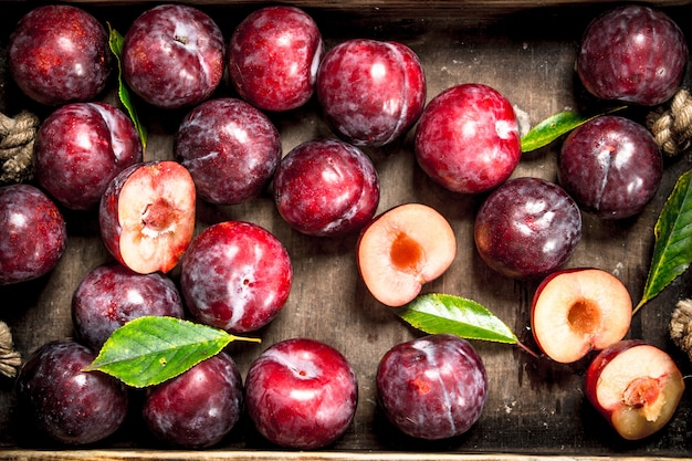 Ripe plums in an old tray. on a wooden background.