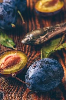 葉、水滴、ビンテージナイフと木製のテーブルに熟したプラム