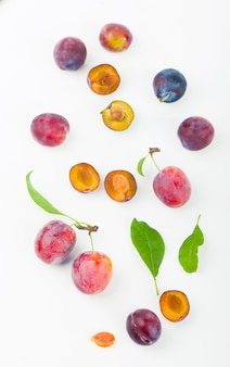 Ripe plums with leaves close up on white surface.
