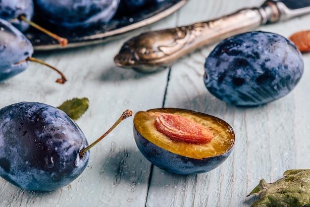 薄木の表面にスライスされた果物、葉、ビンテージナイフで熟したプラム