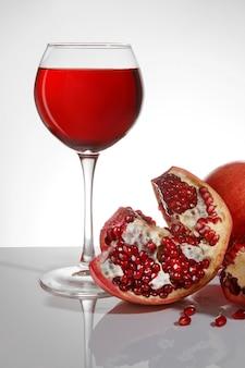 잘 익은 석류와 흰색 배경에 석류 주스와 유리