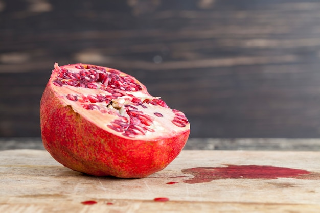 Ripe pomegranate cut with a knife from which juice dripped along a wooden cutting board