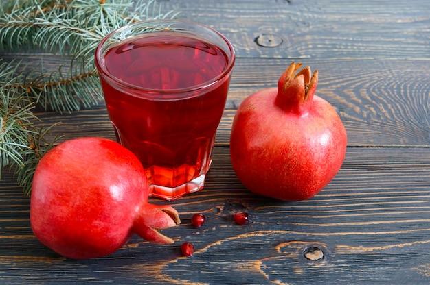 Спелые плоды граната и стакан гранатового сока на деревянном столе. концепция здорового питания.