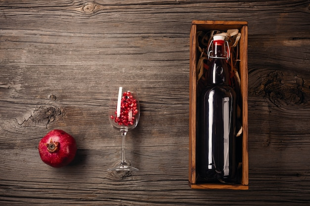 Ripe pomegranate fruit with a glass of wine, a bottle in a box on a wooden background