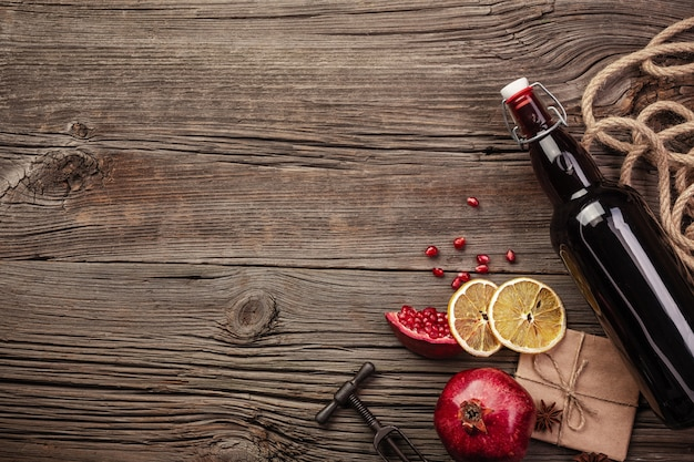 Ripe pomegranate fruit with a glass of wine, a bottle and a corkscrew on a wooden background