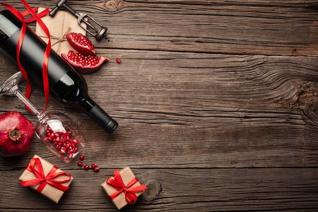 Ripe pomegranate fruit with a glass of wine, a bottle and a gift on a wooden background