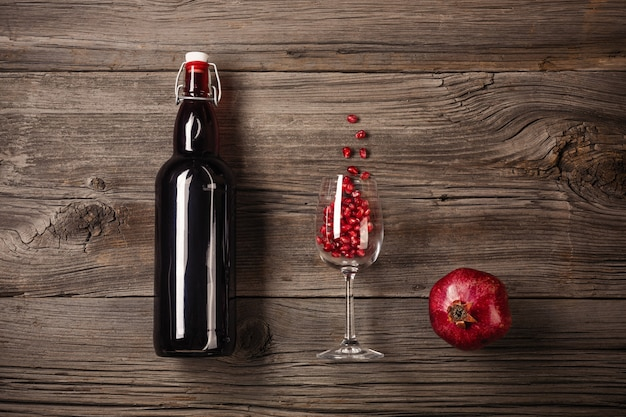 Ripe pomegranate fruit with a glass of wine, a bottle on a wooden background