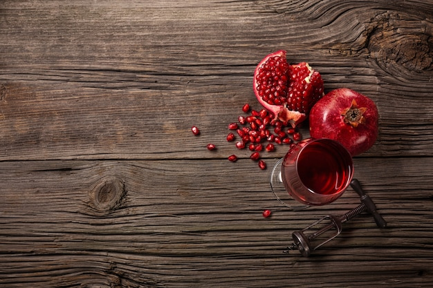 Ripe pomegranate fruit with a glass of wine and a corkscrew on a wooden background
