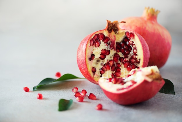 Ripe pomegranate fruit with green leaves on grey concrete background.