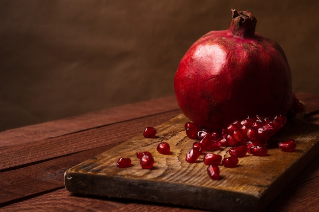 Ripe pomegranate fruit on wooden vintage background