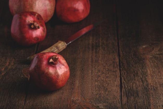 Спелые плоды граната на деревенской деревянной поверхности