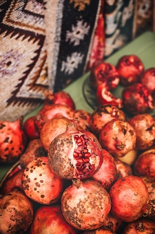 시장 선반에 잘 익은 석류 과일, 과숙 버스트 가넷이 위에 놓여 있습니다