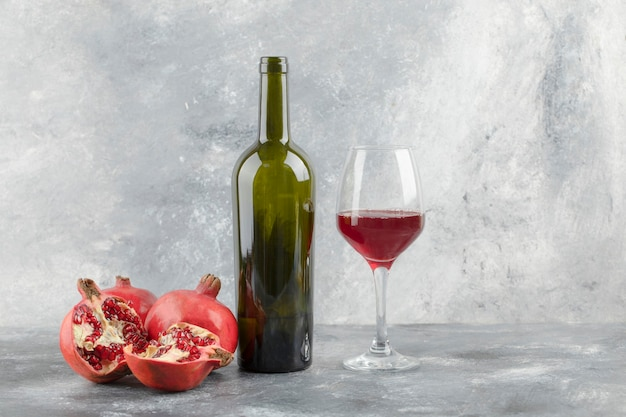 大理石の背景にワインのグラスと熟したザクロの果実。