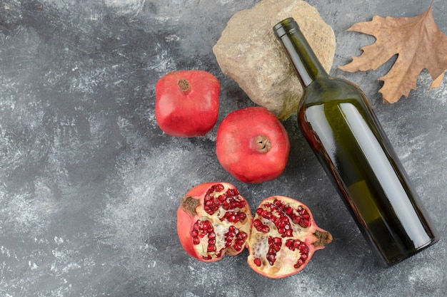 Ripe pomegranate fruits with a bottle of wine on marble background.